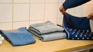 男の人が洗濯物を畳んでいる