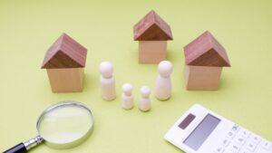 家3つ、4人の模型、虫眼鏡、電卓
